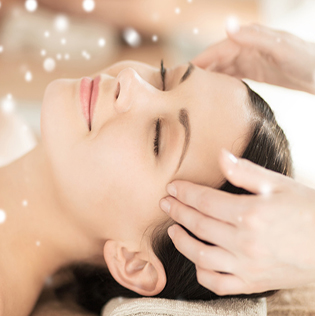 beautiful woman getting face or head massage